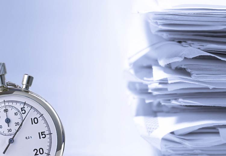 close de um relógio com uma pilha de papeis ao fundo - Por que digitalizar os documentos da sua empresa