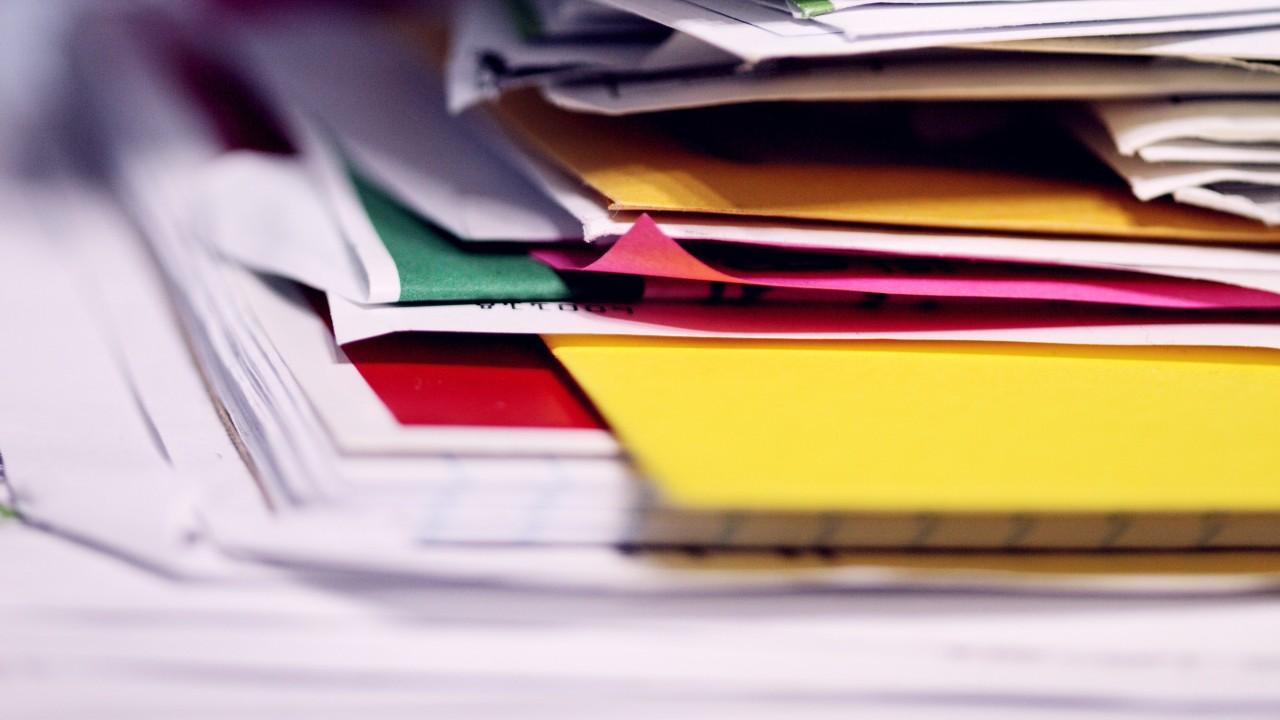 a falta de uma tabela de temporalidade documental resulta em uma pilha de documentos fisicos desorganizados como na foto