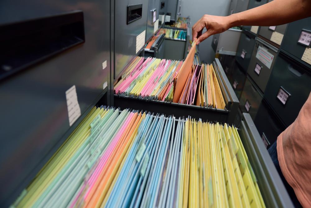 pessoa mexendo em documentos arquivados