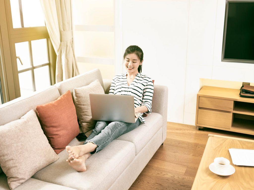 mulher com computador no sofá de casa durante o trabalho home office
