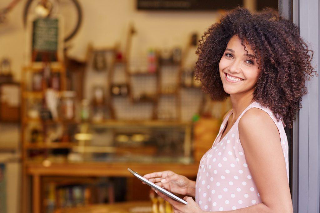 mulher MEi na porta do seu comércio com tablet com certificado digital